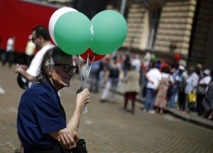 Supporter of the BSP shields herself from the sun with balloons during a rally marking May Day in Sofia