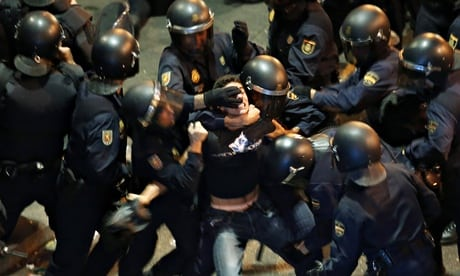 A demonstrator struggles with Spanish police