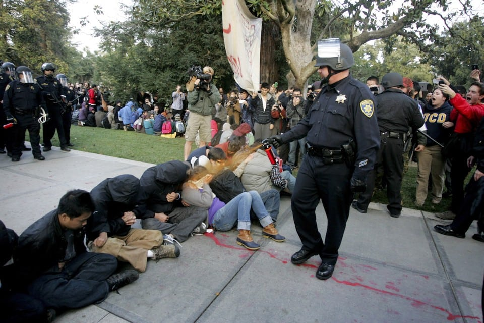 "A University of California Davis police officer pepper-sprays students during their sit-in at an ""Occupy UCD"" demonstration in Davis, California November 18, 2011.  UC Davis Chancellor Linda Katehi apologized to jeering students on November 21 for police use of pepper spray against campus protesters in a standoff captured by video and widely replayed on television and the Internet. Faculty and student critics of Friday's confrontation, some of whom demanded the chancellor's resignation, said it had damaged the school's image and the climate for free expression at the university. Photo taken November 18, 2011.  REUTERS/Brian Nguyen  (UNITED STATES - Tags: CIVIL UNREST EDUCATION CRIME LAW TPX IMAGES OF THE DAY) - RTR2UCTQ"